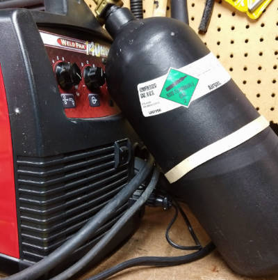 Photo showing the size of a 20 cu. ft. MIG gas cylinder next to a 140 amp MIG welder.
