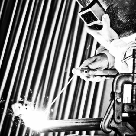 Person stick welding black pipe.