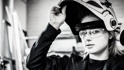 female welding student with helmet
