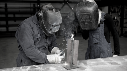 two welding school students working on a project